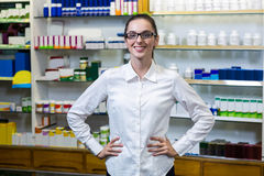 Pharmacist standing with hand on hip in pharmacy. Portrait of pharmacist standing with hand on hip in pharmacy Stock Images