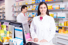 Pharmacist standing at pay desk Royalty Free Stock Photos
