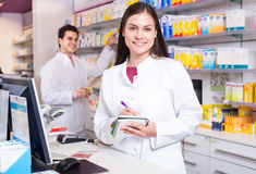 Pharmacist standing at pay desk Royalty Free Stock Images