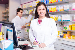 Pharmacist standing at pay desk Royalty Free Stock Photography