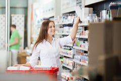 Pharmacist Stocking Shelves. Young pharmacist stocking shelves in pharmacy Stock Photos