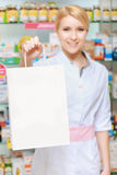 Pharmacist stretches out the paper bag Royalty Free Stock Photography