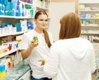 Pharmacist suggesting medical drug to buyer. In pharmacy drugstore Royalty Free Stock Photos