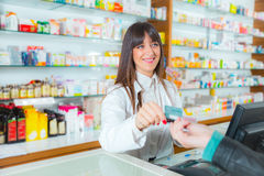 Pharmacist suggesting medical drug to buyer in pharmacy drugstore. Customer pays by credit card stock images