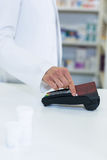 Pharmacist swiping card through payment terminal. In pharmacy Stock Photo