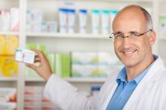 Pharmacist Taking Medicine From Shelf. Confident mature pharmacist taking medicine from shelf at pharmacy royalty free stock images