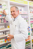Pharmacist taking medicine from shelf Stock Photography