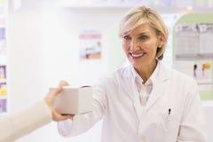 Pharmacist taking medicine to costumer Royalty Free Stock Photo