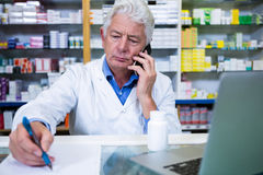 Pharmacist talking on mobile phone while writing prescriptions Stock Photography