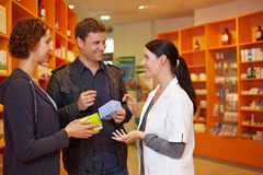 Pharmacist talking to couple. Happy pharmacist talking to a couple in a pharmacy Stock Images