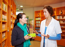 Pharmacist talking to customer. Pharmacist talking to female customer in a drugstore Royalty Free Stock Image
