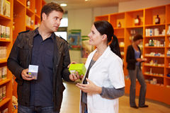Pharmacist talking to man. Pharmacist talking to a men in a pharmacy Royalty Free Stock Photos