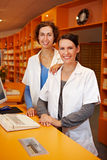 Pharmacist trainee in drugstore. Smiling pharmacist trainee in drugstore with a pharmacist Royalty Free Stock Photo