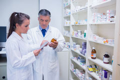 Pharmacist and trainee talking together about medication Stock Photos