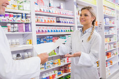 Pharmacist and trainee talking together about medication Royalty Free Stock Photo