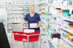 Pharmacist Updating Stock In Laptop At Pharmacy Royalty Free Stock Photography
