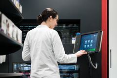 Pharmacist using a computer while managing the drug stock in pha. Low-angle rear view of an experienced female pharmacist using a computer while managing the Royalty Free Stock Photos