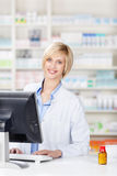 Pharmacist Using Computer At Pharmacy Counter Royalty Free Stock Photography