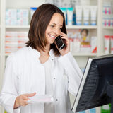 Pharmacist Using Cordless Phone While Looking At Computer Royalty Free Stock Photo