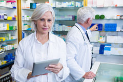 Pharmacist using digital tablet and co-worker checking medicines Stock Image
