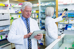 Pharmacist using digital tablet and co-worker checking medicines Stock Photography