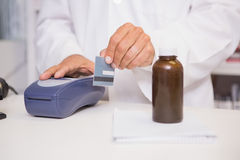 Pharmacist using keypad with credit card. In the pharmacy Stock Photography