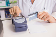 Pharmacist using keypad and holding credit card Stock Photography