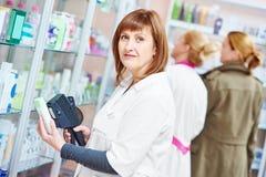Pharmacist using labeling gun in pharmacy drugstore Royalty Free Stock Photo