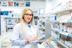 Pharmacist using laptop and internet technology in pharmacy drugstore. Pharmacist using modern laptop and internet technology in pharmacy drugstore Royalty Free Stock Photography
