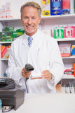 Pharmacist using machine and holding medicine Royalty Free Stock Photography