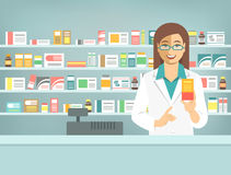 Pharmacist woman with medicine at counter in pharmacy. Pharmacist at counter in pharmacy. Woman druggist stands opposite shelves with medicines and points to box Royalty Free Stock Photo