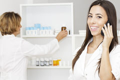 Pharmacist woman by  phone Royalty Free Stock Images