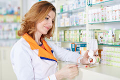 Pharmacist woman picking medicine Royalty Free Stock Photos