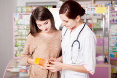 Pharmacist woman showing product to custumer Royalty Free Stock Photo