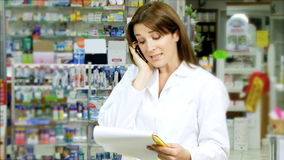 Pharmacist woman working in pharmacy on the phone Stock Photos