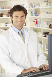 Pharmacist working on computer in pharmacy Stock Photography
