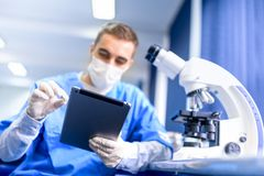 Pharmacist working on prescription drugs with modern tablet Royalty Free Stock Images