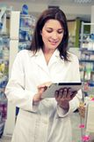 Pharmacist working with tablet in pharmacy Royalty Free Stock Photo