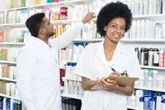 Pharmacist Writing On Clipboard While Colleague Arranging Produc. Portrait of female pharmacist writing on clipboard while colleague arranging products in royalty free stock photography