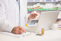 Pharmacist writing on clipboard and holding medication Royalty Free Stock Images