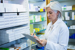 Pharmacist writing on clipboard Royalty Free Stock Photo