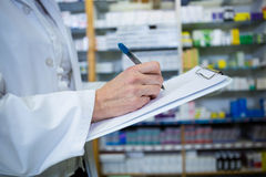Pharmacist writing on clipboard. In pharmacy stock images