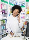 Pharmacist Writing On Clipboard While Using Telephone Stock Photo