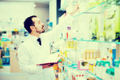 Pharmacist writing down assortment of drugs Stock Photography