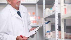 Pharmacist writing on his clipboard Stock Image