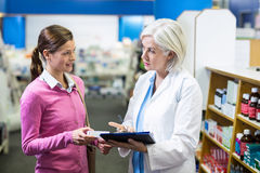 Pharmacist writing prescriptions for customer on clipboard Stock Photo