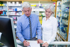 Pharmacist writing prescriptions for medicines Stock Image