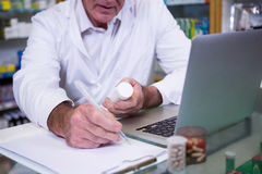 Pharmacist writing prescriptions for medicines Royalty Free Stock Image