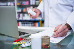 Pharmacist writing prescriptions for medicines. In pharmacy Royalty Free Stock Photos