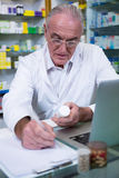 Pharmacist writing prescriptions for medicines Stock Photos